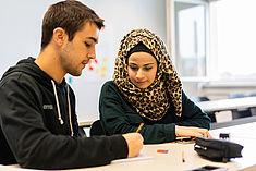 Ein Student erklärt einer Studentin etwas an einem Tisch