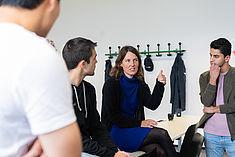 Eine Gruppe Studierender unterhält sich in einem Kursraum