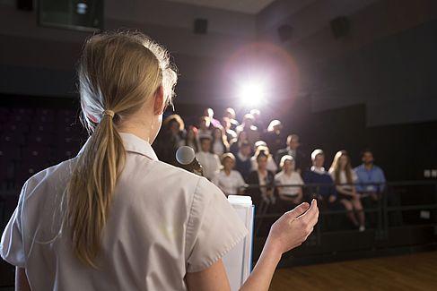 Schülerin hält Vortrag vor Publikum