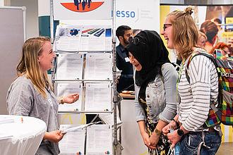Zwei Studentinnen im Gespräch mit Unternehmensvertreterin