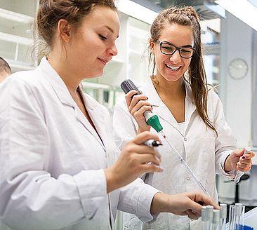 Zwei Studentinnen in Kitteln im Labor