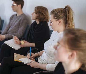 Studentin macht in einem Seminar Notizen