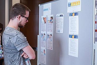 Student schaut sich die Anzeigen an der Jobwall an