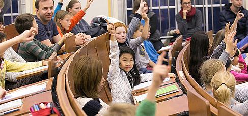 Kinder melden sich im Vorlesungssaal