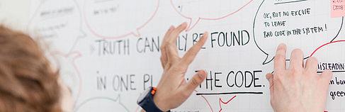 Studentin vor einem Plakat, auf dem etwas über Code steht