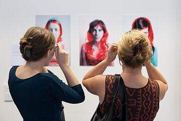 Zwei Frauen betrachten durch 3D-Brillen ein Ausstellungsstück