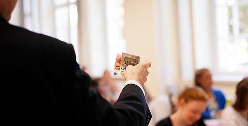 Professor hält in einer Lehrveranstaltung Banknoten in der Hand