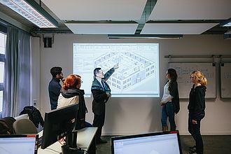Professor erklärt Studierenden eine Bauskizze, die von einem Beamer an die Wand geworfen wird