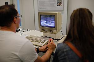 Besucher an einem alten Computer