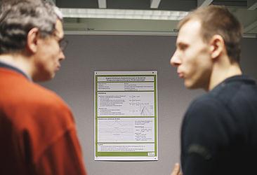 Zwei Wissenschaftler vor einem Poster
