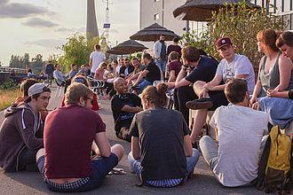 Studierende sitzen zusammen und tauschen sich in geselliger Runde aus