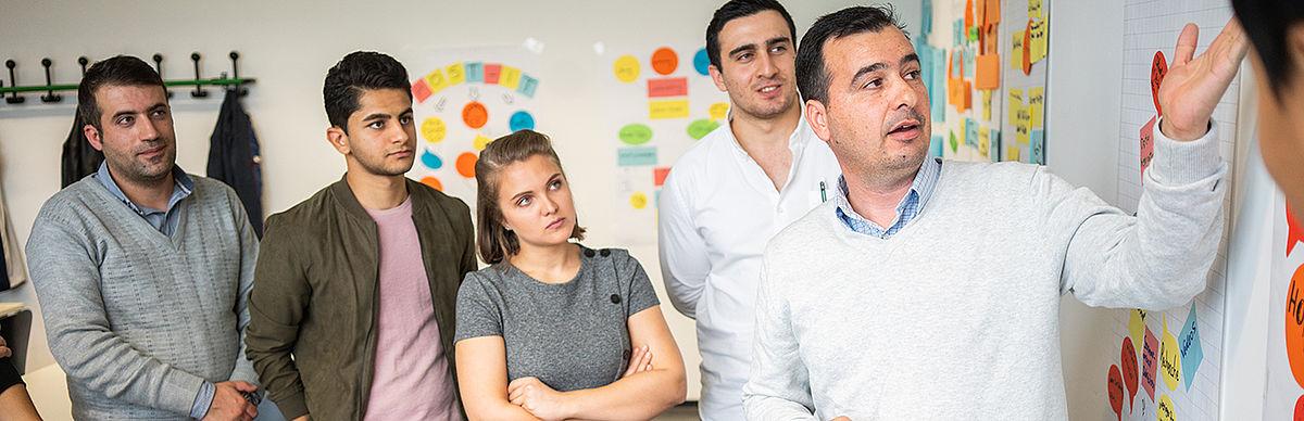 Ein Student erklärt anderen Studierenden etwas an einer Pinnwand