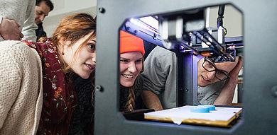 Drei Studierende schauen in einen 3D-Drucker